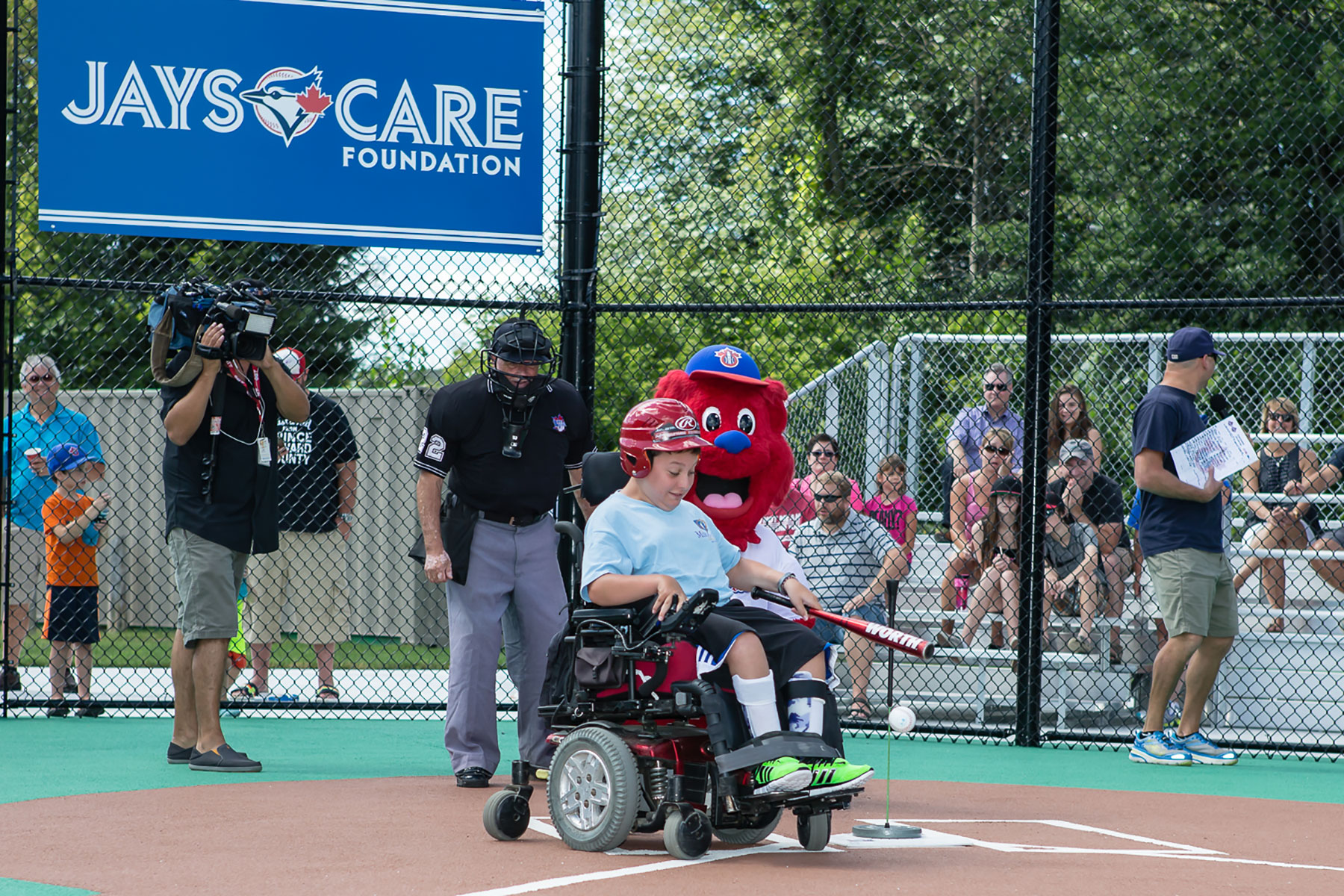 A player in a wheelchair taking advantage of the accessibly designed baseball diamond at Miracle League of Ottawa field.